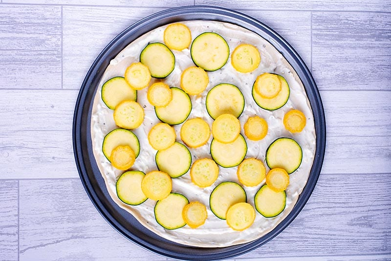 A pizza base with a yogurt sauce and slices of zucchini