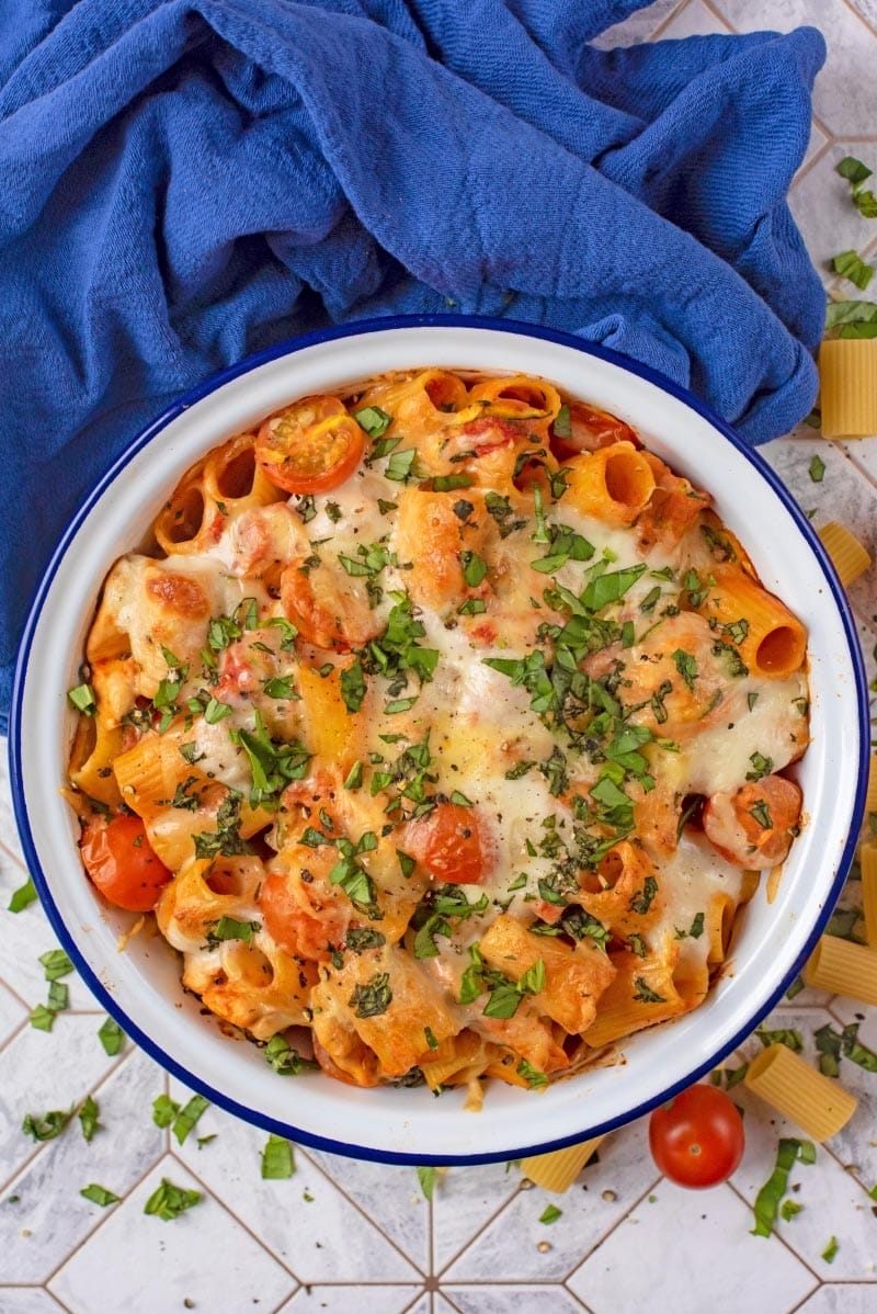 Pasta bake in a white bowl, next to a blue towel