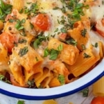 A white bowl with a blue rim containing Creamy Tomato Chicken Pasta Bake