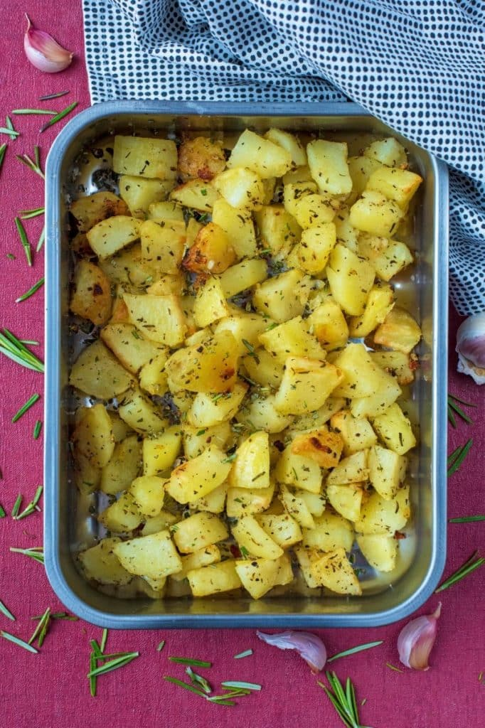 A roasting tin containing Garlic and Rosemary Roasted Potatoes