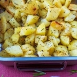 A roasting tin containing cubes of roasted potato