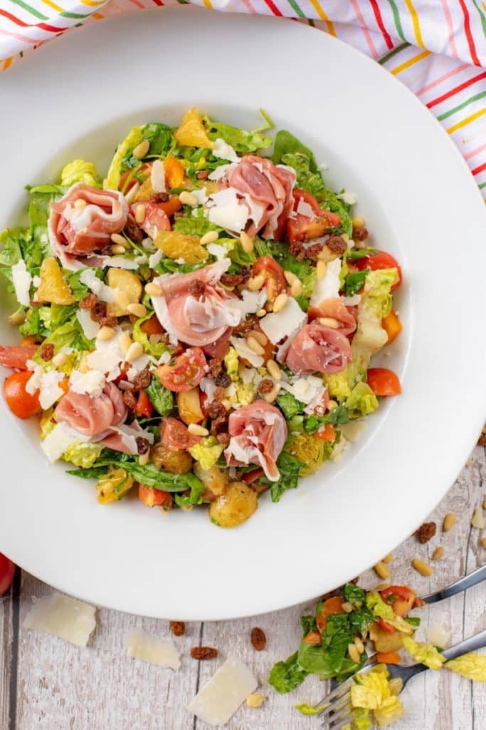 Parma ham sat upon a chopped salad containing leaves, tomatoes, fruit and nuts