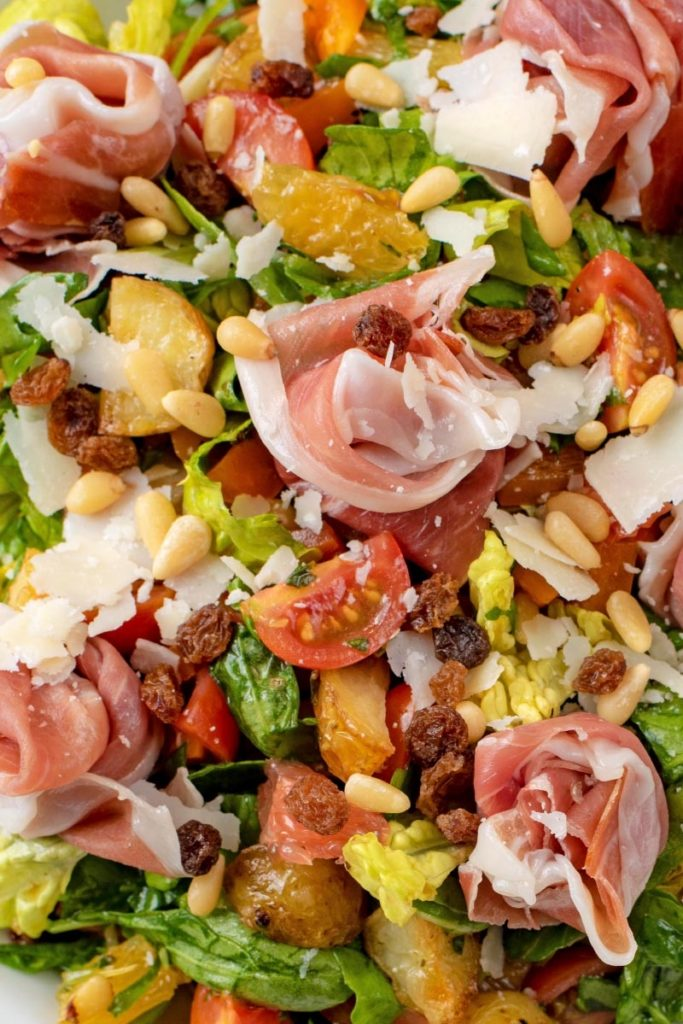 A chopped salad of lettuce, tomatoes, potatoes, fruit, nuts and parma ham
