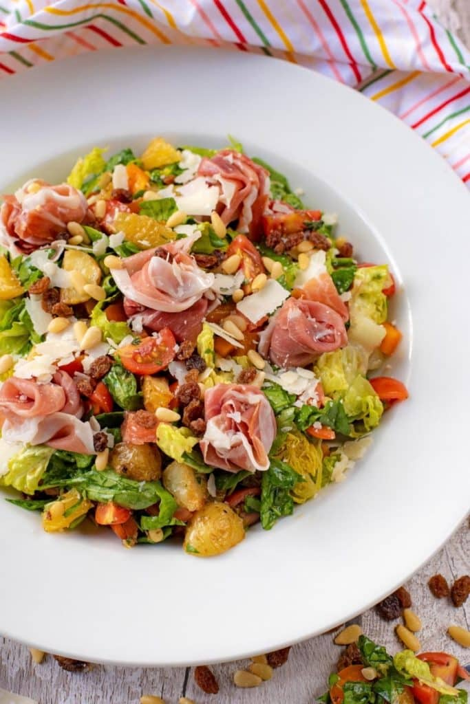 A large white bowl containing Italian Chopped Salad with Parma Ham. Striped towel in the background