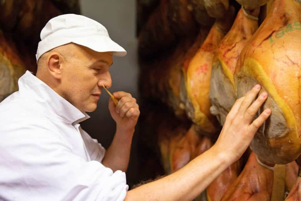 A man in white clothes smelling Parma ham to check its maturity