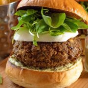A Quorn pesto burger in a brioche bun sat on a wooden serving board. A small jar of sauce is next to it