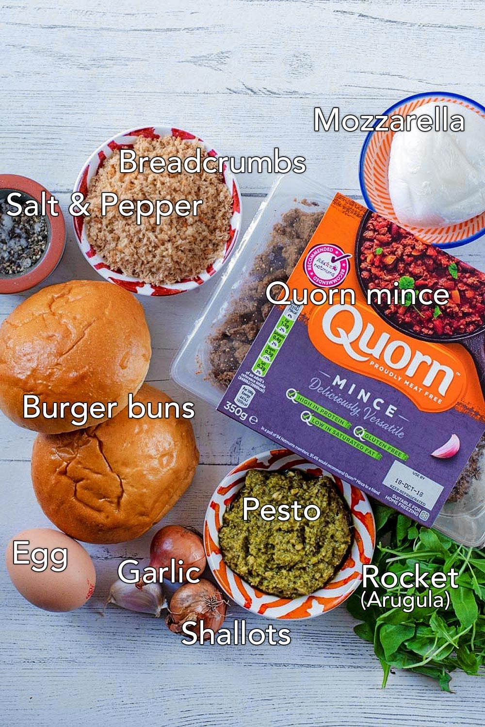 A pack of quorn mince, two burger buns, an egg, mozzarella, dish of breadcrumbs, salad, shallots and garlic. All on a wooden surface