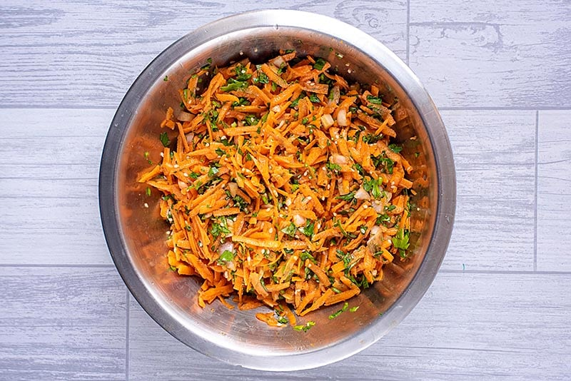 A large metal bowl full of carrot and coriander salad