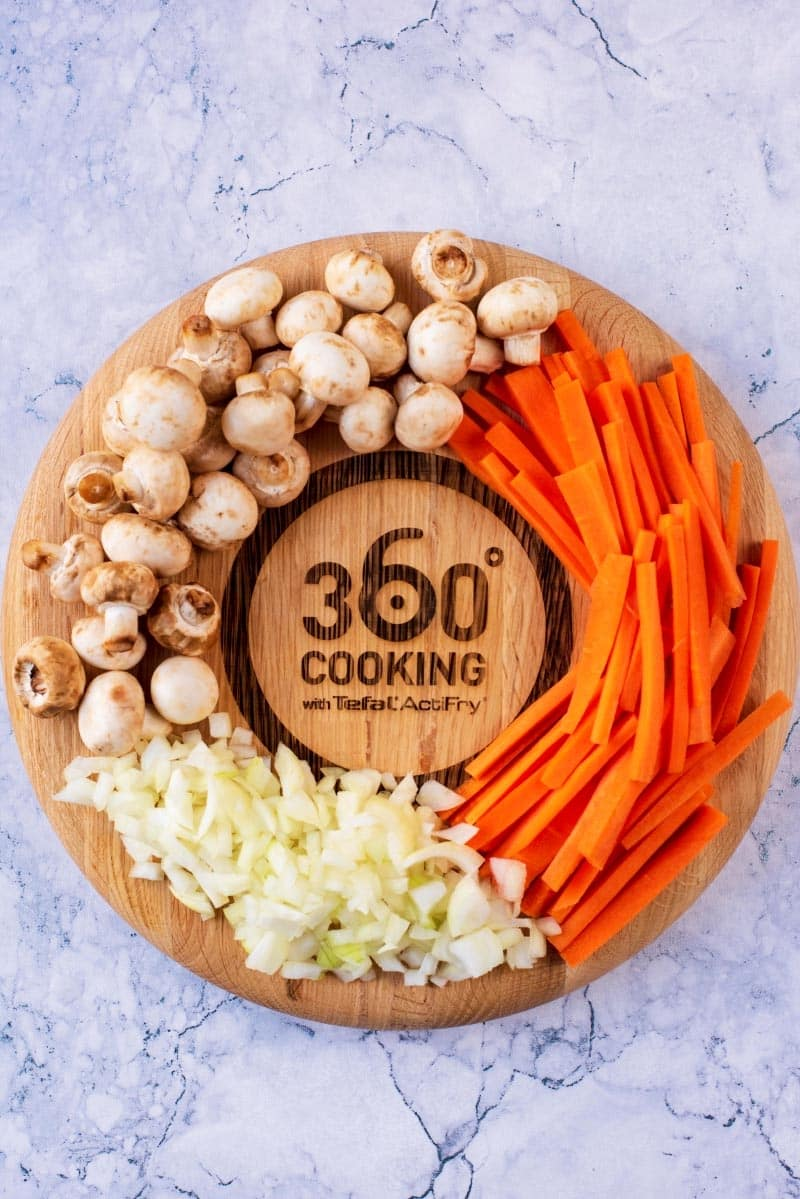 Button mushrooms, chopped onions and sliced carrots on a circular chopping board