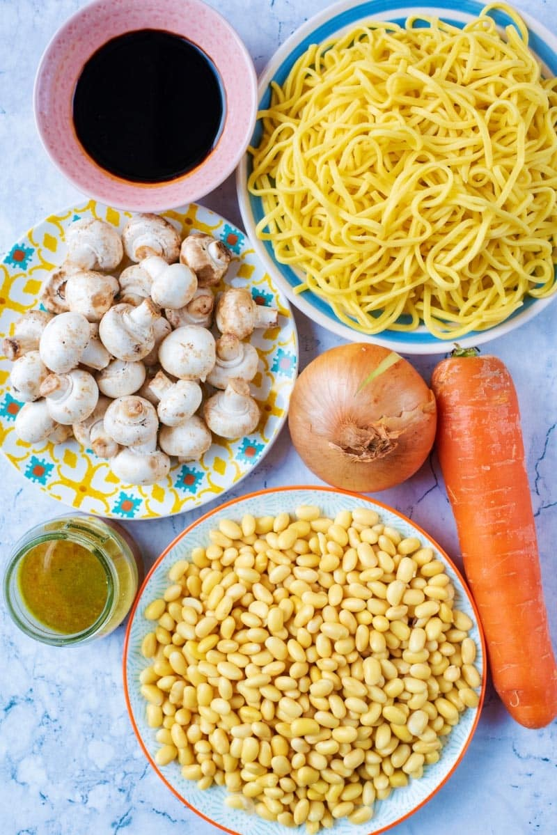 Noodles, mushrooms, soy beans, a carrot, onion, stock and soy sauce, all on a marble surface