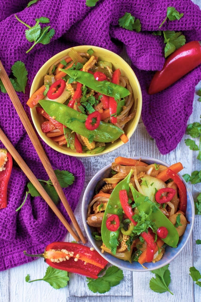 Vegetable Stir Fry in two bowls next to a purple towel