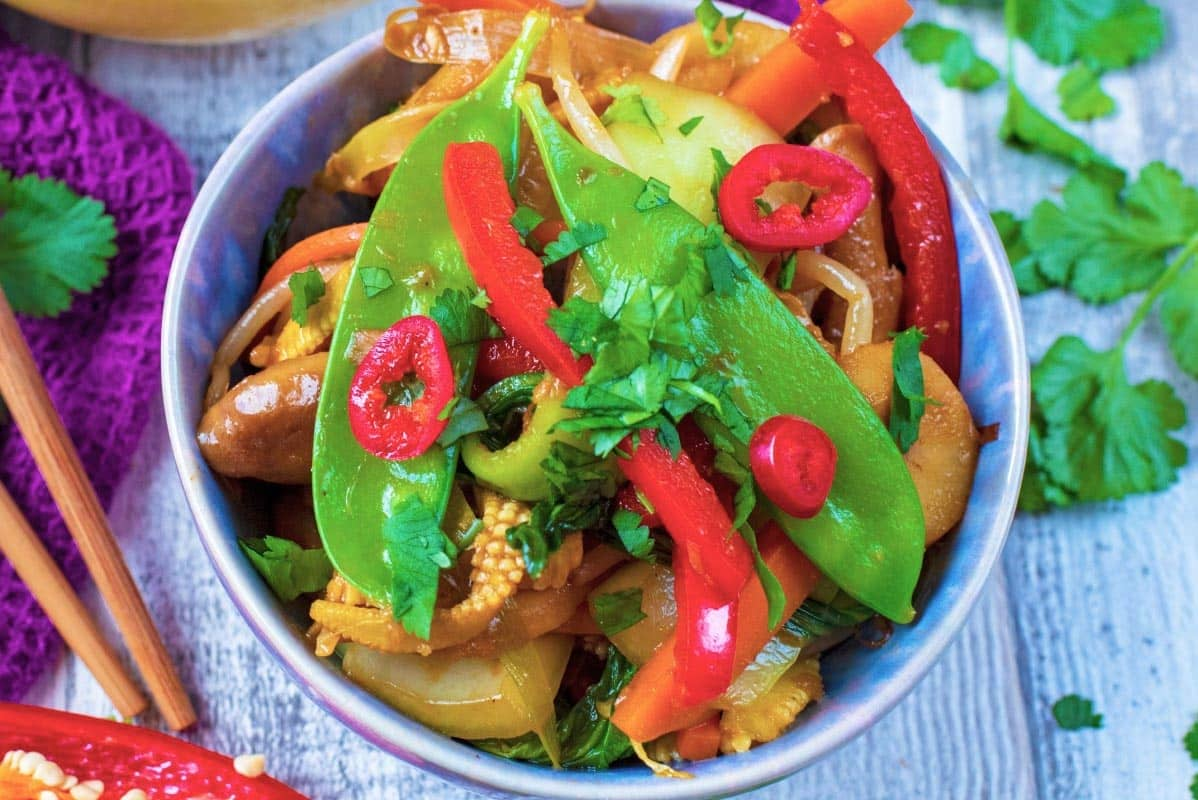 Mangetout, chilli and coriander on top of a bowl of stir fry