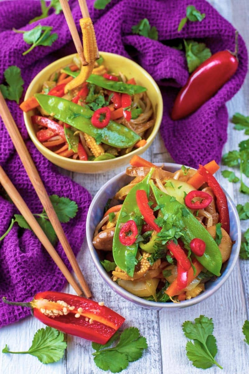 Vegetable stir fry in two bowls next to chopsticks