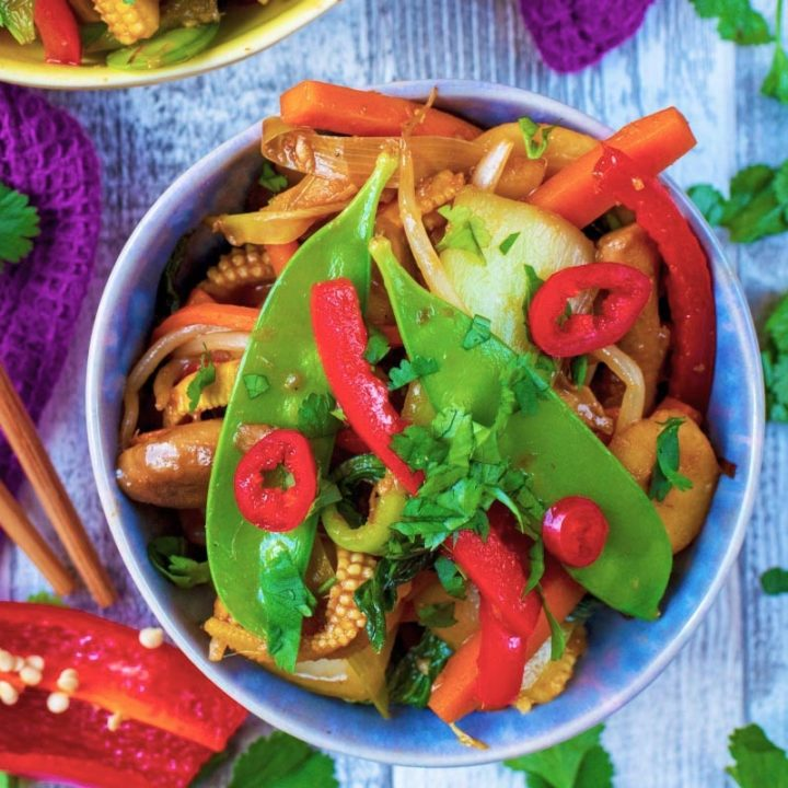 A bowl of easy vegetable stir fry, topped with mangetout and chilli