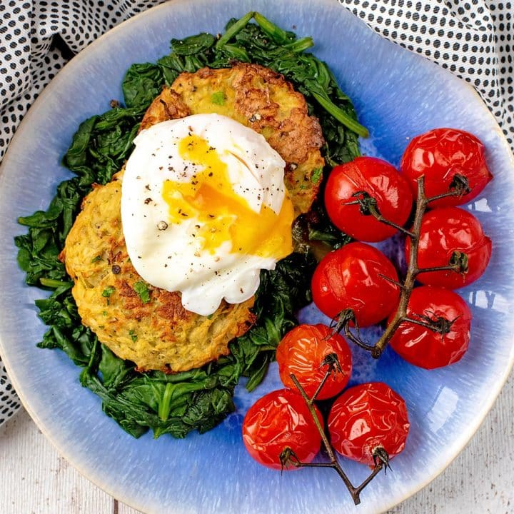 A poached egg, yolk running out, on top of two oven baked baked hash browns. Roasted tomatoes next to them
