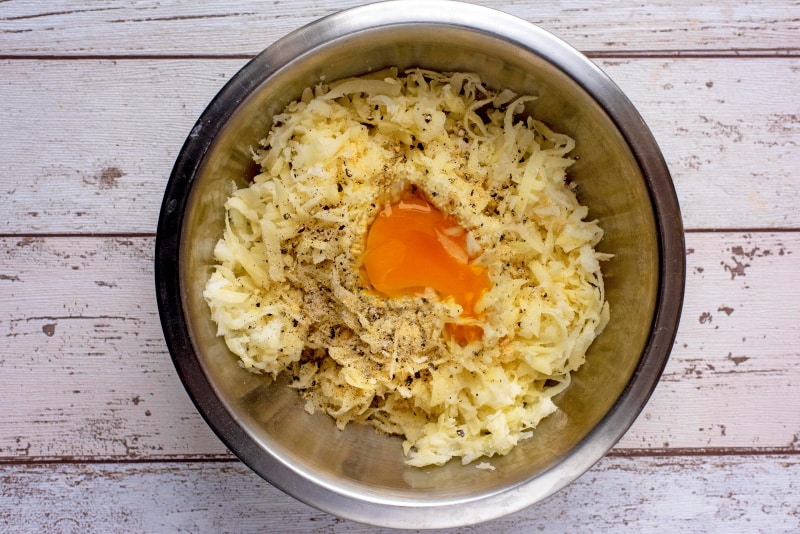 A stainless steel mixing bowl with grated potato, onion, an egg and seasoning