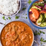 Beef curry in a balti dish next to a bowl of rice and a side salad