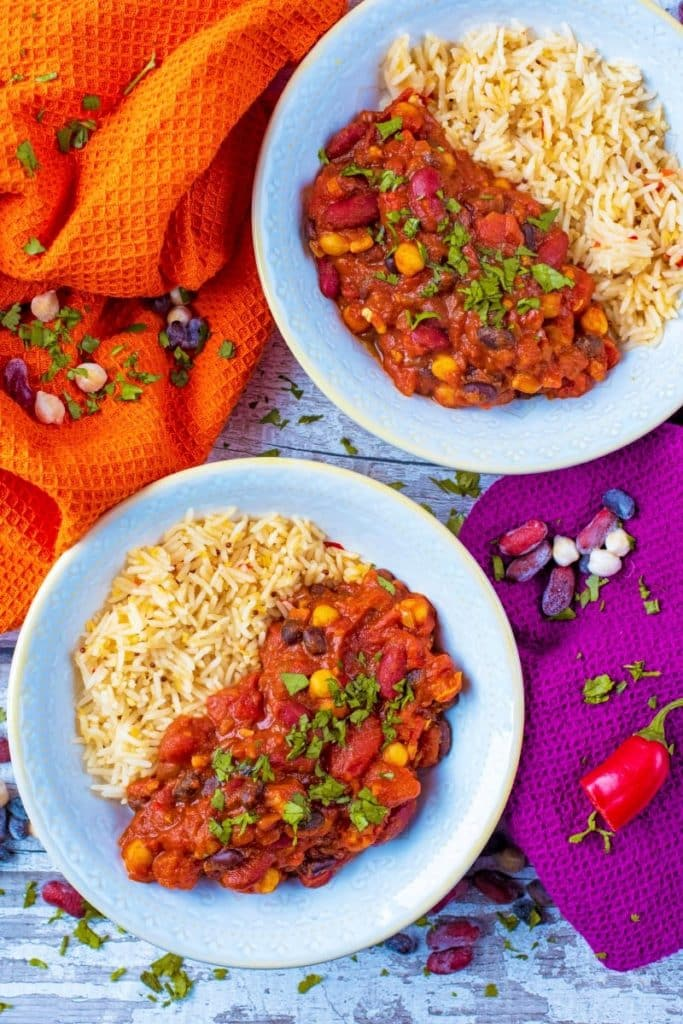 Two bowls of curry and rice with orange and purple towels