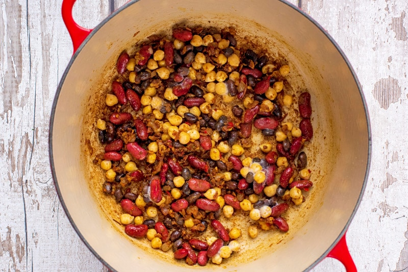 A large red pan with cooked shallots, chili, garlic, ginger, curry powder and mixed beans