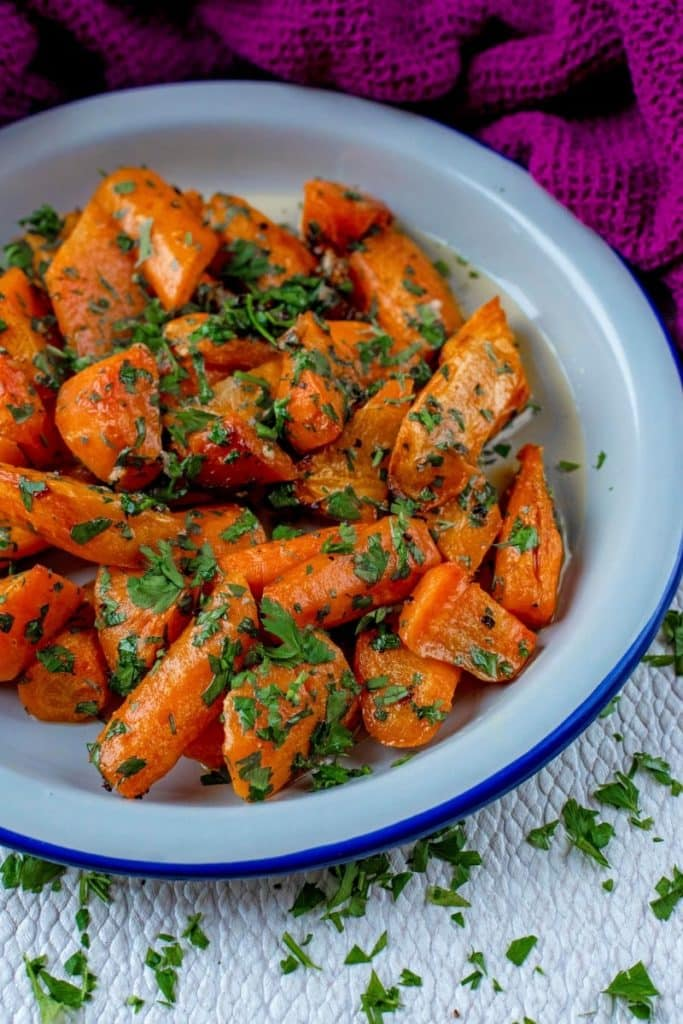 Carrots and herbs in a blue rimmed white bowl
