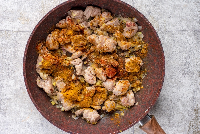 Cooked chunks of lamb, chopped onions, minced garlic and spices cooking in a frying pan