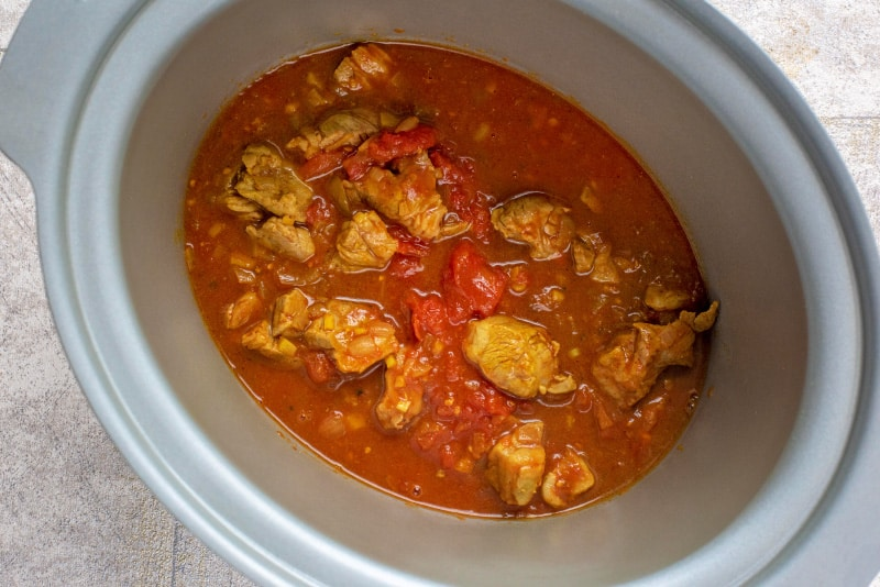 A slow cooker crockpot containing chunks of lamb in a rich tomato sauce