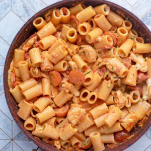 A frying pan containing pasta and chicken in a creamy tomato sauce