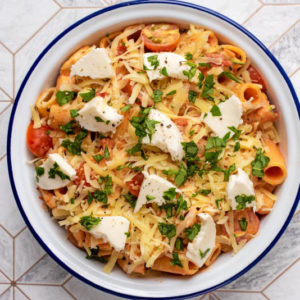 A baking dish containing creamt chicken pasta topped with cheese