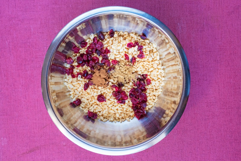 A metal mixing bowl with rice cereal, dried cranberries and spices