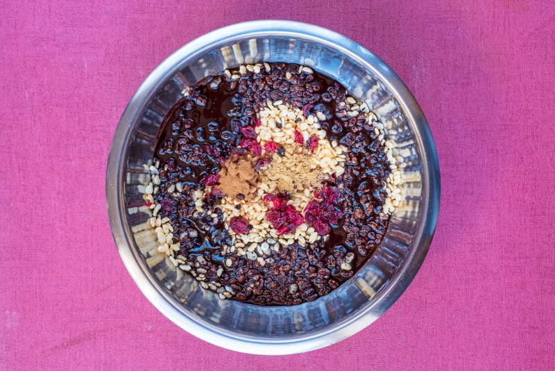 A metal mixing bowl with rice cereal, dried cranberries and chocolate sauce