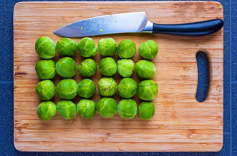Twenty Four Brussels Sprouts on a wooden chopping board with a large knife