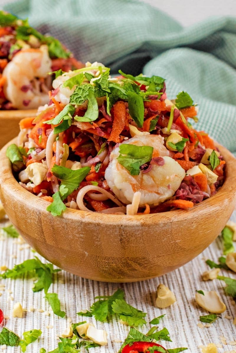A wooden bowl of noodles topped with cooked king prawns