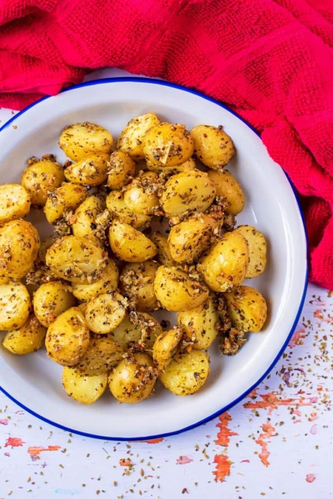 Italian Roasted Potatoes in a white , blue rimmed dish