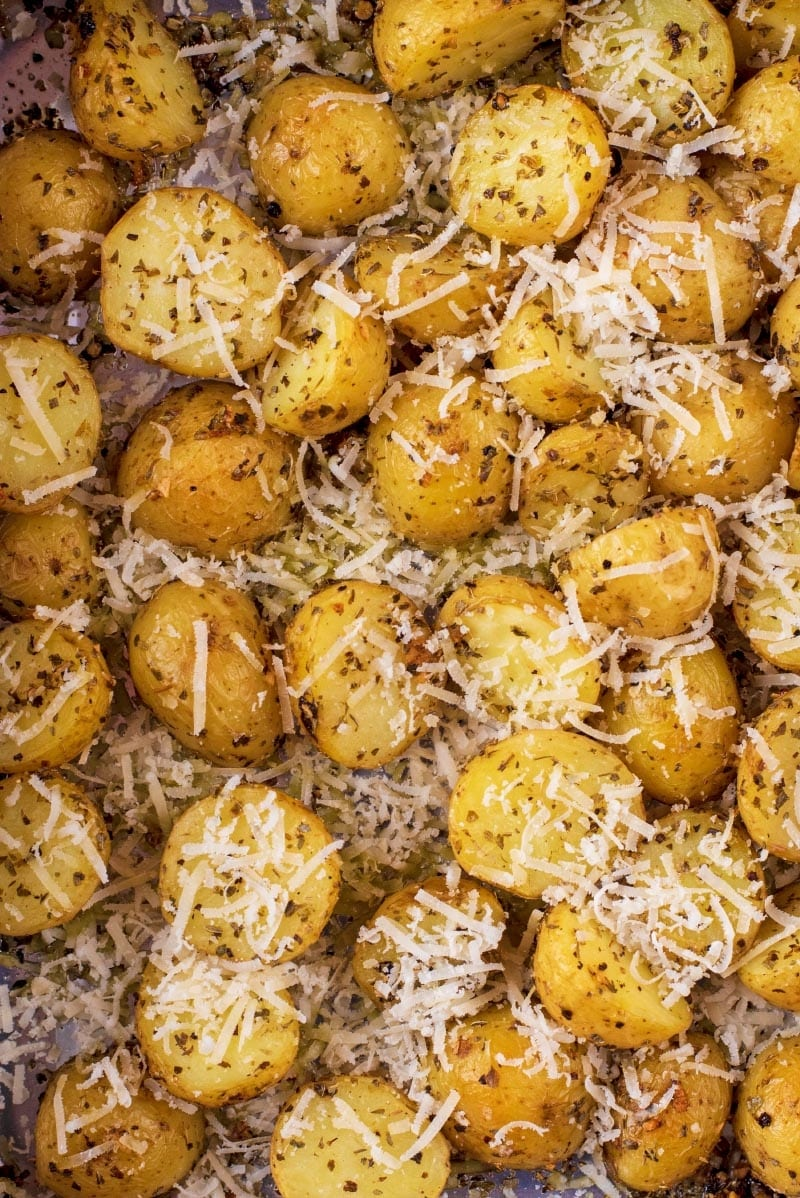 Roasted new potatoes covered in herbs and grated cheese