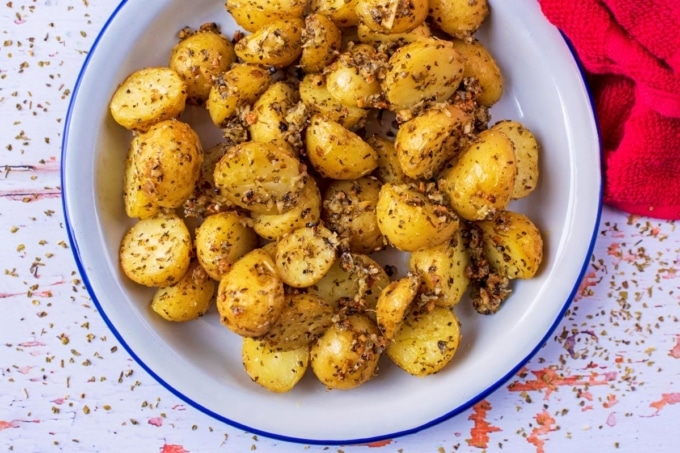 Italian Parmesan Roasted Potatoes in a white dish next to a red towel