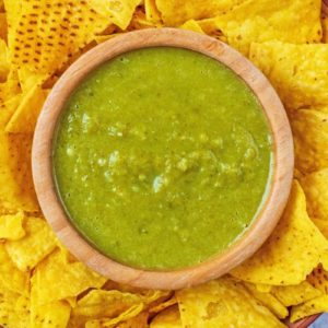 A bowl of Jalapeno Sauce surrounded by tortilla chips