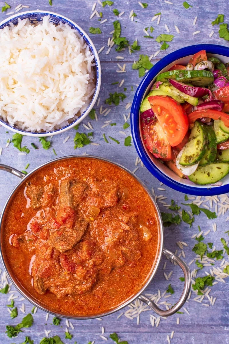 Beef Curry in a Balti dish next to a bowl of rica and a chopped salad