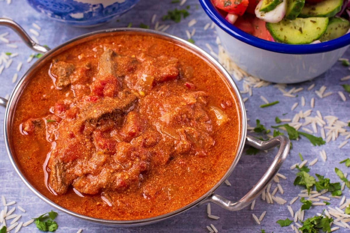 A deep red Slow Cooker Beef Curry in a metal dish