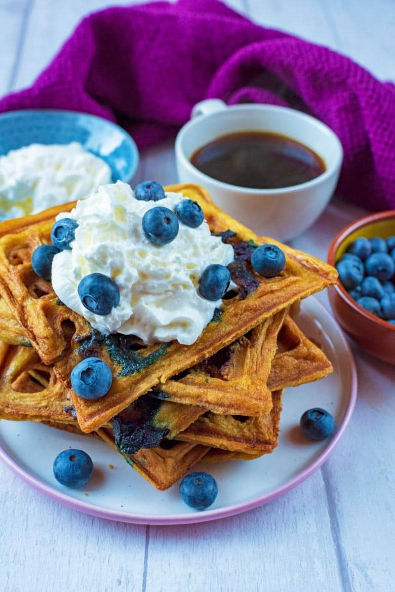 A plate of blueberry waffles topped with whipped cream and blueberries