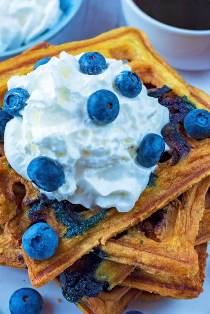 A stack of waffles with a dollop of cream and scattered blueberries