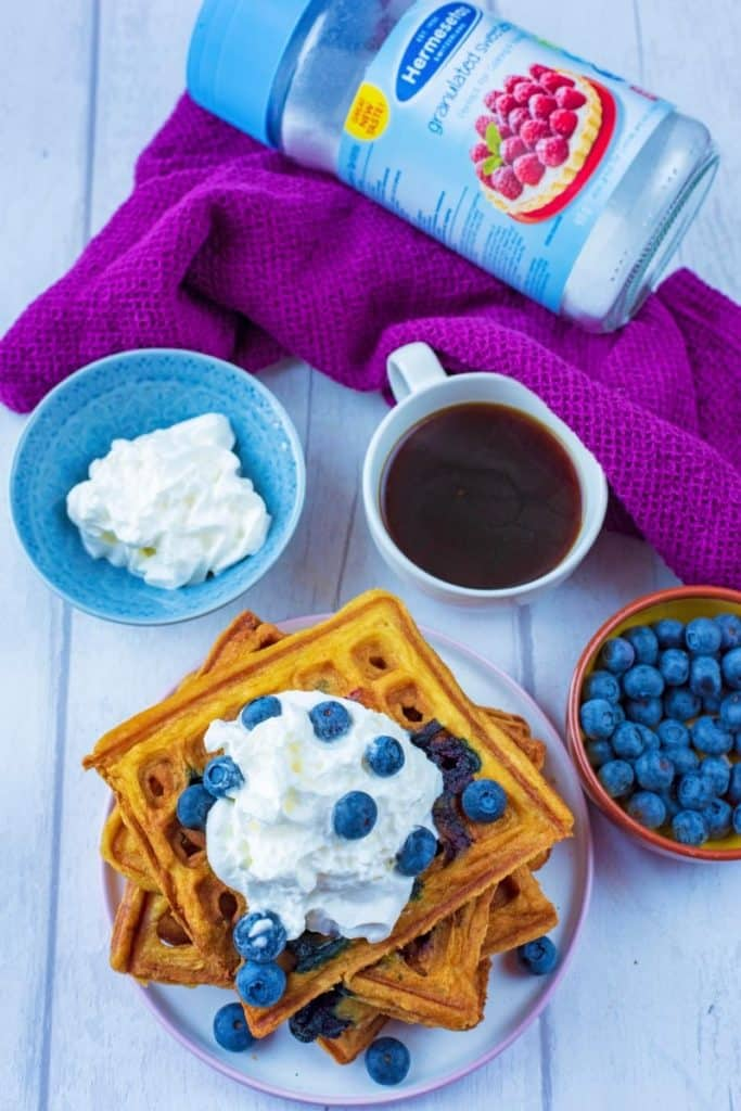 A plate of blueberry waffles with a cup of coffee, bowl of blueberries and a jar of Hermesetas sweetener
