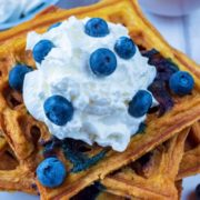 A pile of Blueberry Waffles on a white plate with cream and blueberries on top