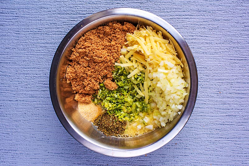 A mixing bowl containing mashed broccoli, breadcrumbs, grated cheese, chopped onion and herbs