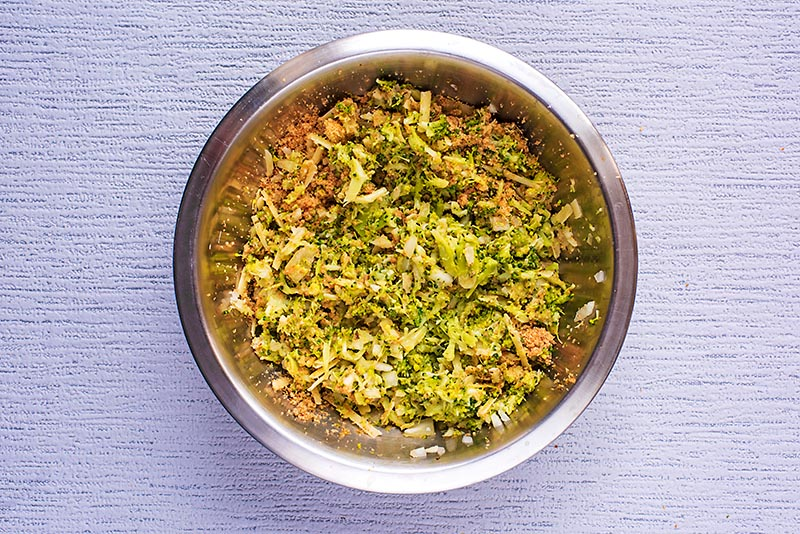 Broccoli, onion, breadcrumbs and cheese all mixed together in a bowl