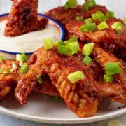 Oven Baked BBQ Chicken Wings on a white plate. One wing is being dipped into a pot of ranch sauce