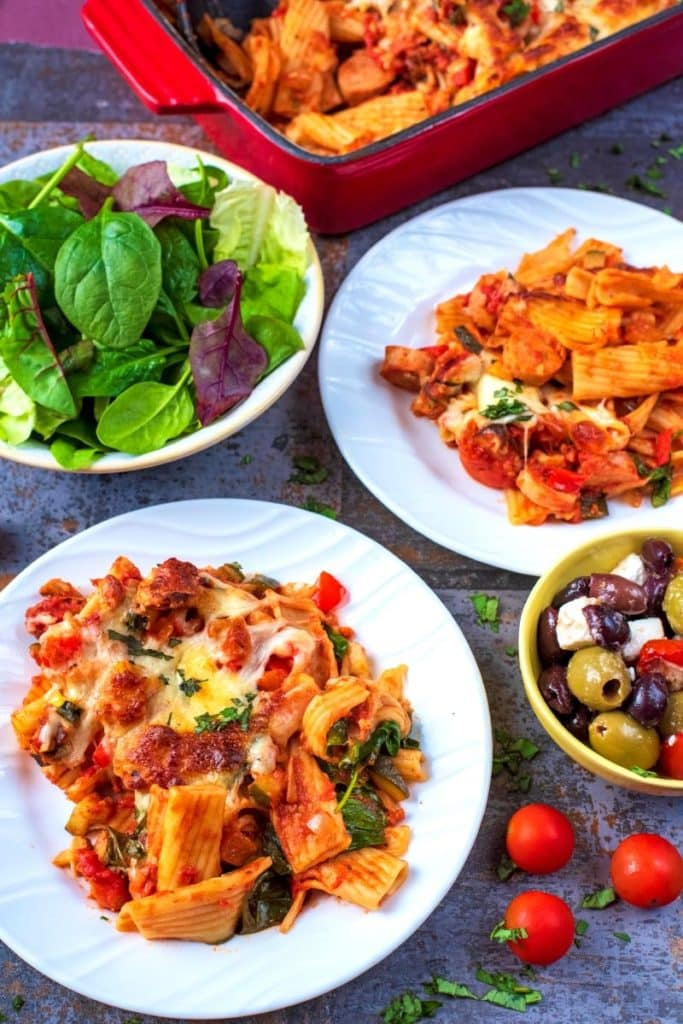 Pasta bake on two plates with a bowl of salad and a bowl of mixed olives