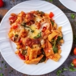 Sausage Pasta Bake on a white plate with cherry tomatoes scattered around