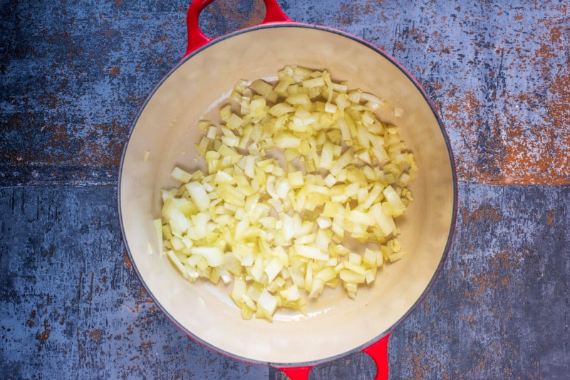 Onions and garlic cooking in a large red pot
