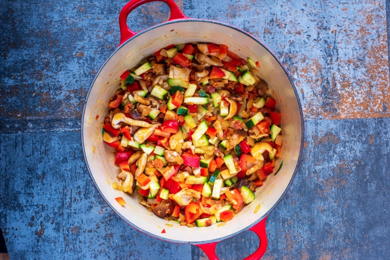 Chopped vegetables cooking in a large red pan