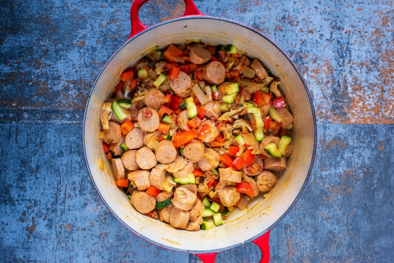 Chopped vegetables and sliced sausage cooking in a large red pan